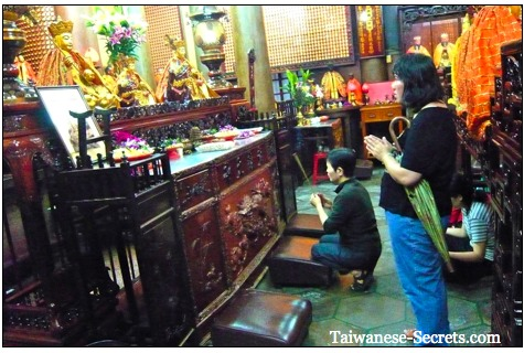 chinese people praying in a chinese temple