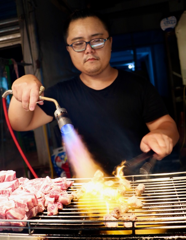 Cooking meat with a blowtorch at a night market in Taiwan