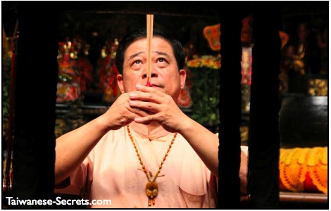 chinese man praying and burning incense in a temple